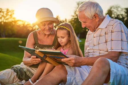 Niña con abuelos, álbum de fotos. Personas que miran fotos al aire libre. Hace muchos años.