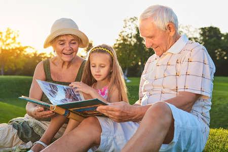 Personas que miran a través del álbum de fotos. Chica caucásica con abuelos al aire libre. Páginas del pasado.