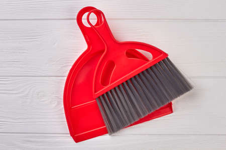 Red dustpan and brush on wooden background. Plastic scoop and brush on white wooden floor. Products for cleaning.