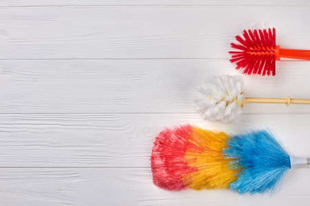 Colorful brushes for house cleaning. House cleaning supplies on white wooden background, copy space. Cleaning service concept.