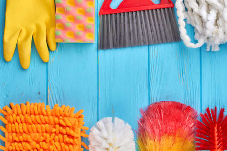 Variety of colorful house cleaning products. Set of cleaning items on blue wooden background, copy space. Household chore concept. Stock Photo