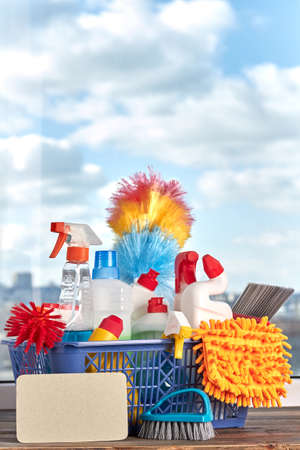 Group of products for cleaning in basket. Set of house cleaning items on blue sky background. Blank paper card for text. Spring cleaning concept.