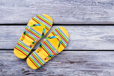 Yellow striped flip flops, top view. Flat lay. Grey wooden desk surface background.