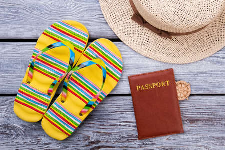 Beach flat lay with passport. Travel and beach concept. Flip-floppers, passport and straw hat. Grey wooden surface background. Stock Photo