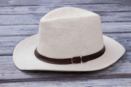 White straw hat with belt. Wooden desk surface background.