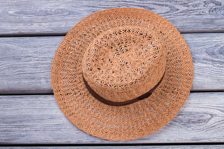 Top view brown straw hat. Wooden desk surface background.