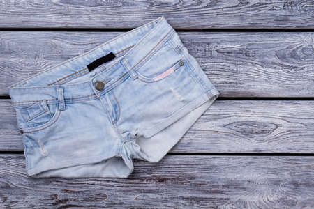 Denim female shorts.Flat lay. Grey wood surface background.
