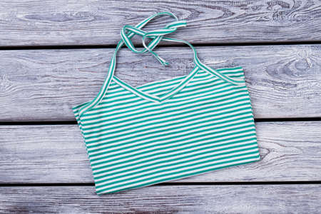 Green female striped blouse. Folded sommer wear for woman. Grey wood surface background. Stock Photo