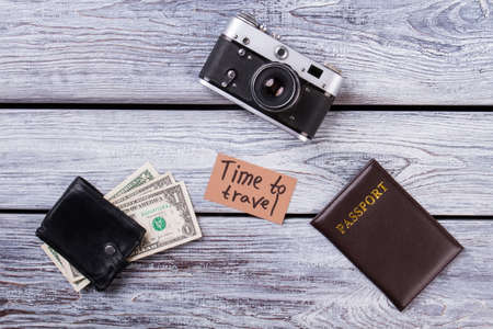 Time to travel essentials. Flat lay, top view. Photo camera, passport, and wallet with cash on wooden table.