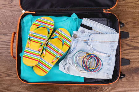 Women summer beach clothes in suitcase. Top view, flat lay. Imagens