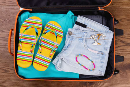 Summer female clothes in suitcase. Beach concept flat lay, top view.