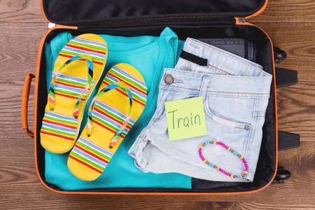 Packed summer female clothes for resort. Opened suitcase for travel.Top view, flat lay. Imagens
