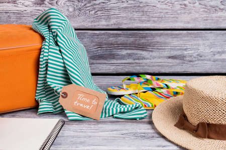 Summer female clothes for travel. Wooden desk surface.