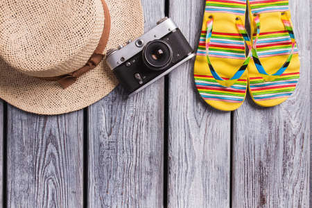 Straw hat, vintage photo camera and flip-flops. Top view, flat lay, summer, beach and travel concept. Wooden desk surface. Imagens