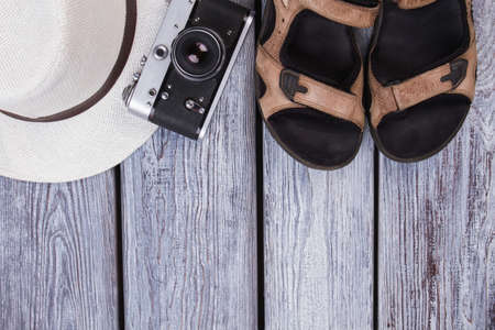 Summer traveler attributes with copyspace. Male sandals, vintage photo camera and white straw hat. Wooden desk surface background.