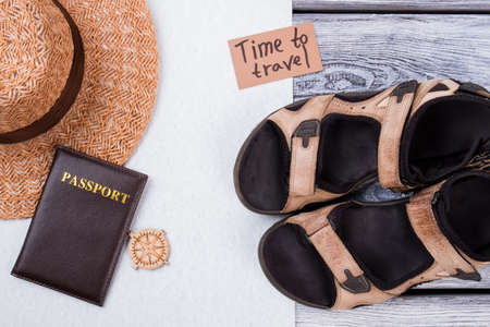 Time to travel and beach rest concept flat lay. Summer footwear, straw hat and passport on white and wooden background. Reklamní fotografie