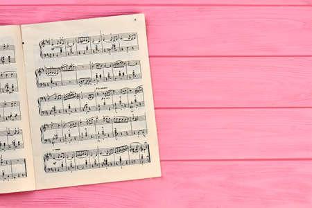 Hoja con notas musicales, espacio de copia. Notas musicales sobre fondo de madera rosa.