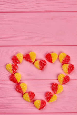 Heart made of sugary candies, top view. Colorful candies forming heart shape on pink wooden background, copy space. Valentines holiday concept. Stock Photo
