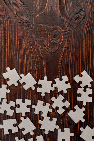 Jigsaw puzzles parts and copy space. Blank cardboard puzzles on wooden background and text space.