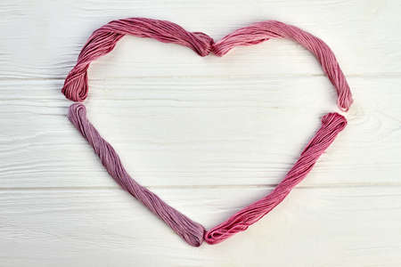 Shape of heart from colorful threads. Bundles of threads forming heart on white wooden background with copy space.