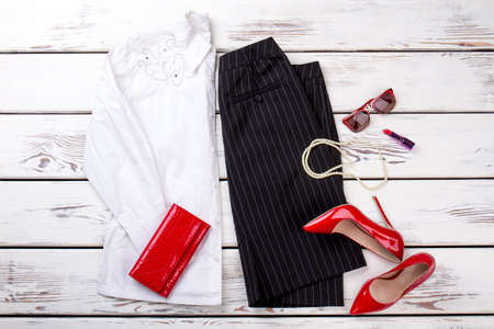 Flat lay female clothes and accessories. White blouse, black skirt, red heels and purse. Feminine fashion background.