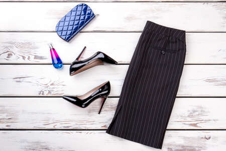 Women classic skirt, heels and accessories. Black leather high-heeled shoes, perfume and purse on wooden background. Female black pencil skirt and shoes.