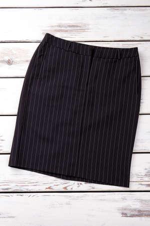 Female black casual skirt. Women striped classic skirt on white wooden shelf. Feminine formal apparel background. Stock Photo