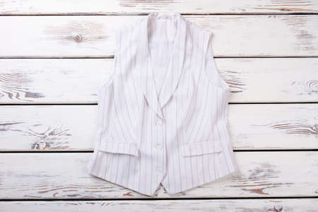 Female white formal vest with black stripes. Women waistcoat on white wooden background. Ladies office outfit. 스톡 콘텐츠