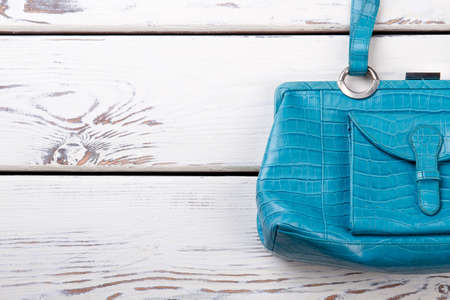 Female blue leather handbag, copy space. Women stylish bag on white wooden background. Feminine fashion accessory. Фото со стока