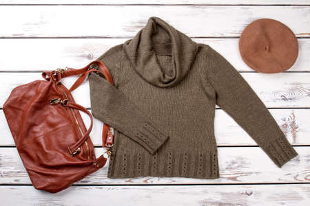 Flat lay female clothes and accessories. Women khaki color pullover and brown leather handbag. Ladies fashion style.
