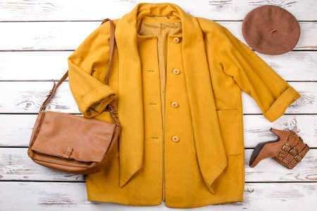 Set of women fashionable topcoat and accessories. Stylish female overcoat, brown handbag, boots and beret. Flat lay feminine classy outfit.