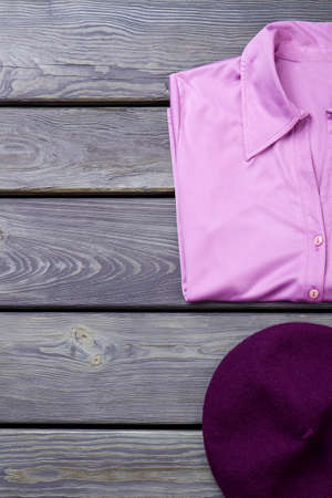 Female elegant satin shirt. Women beautiful purple blouse and beret on old wooden background, space for text. Reklamní fotografie