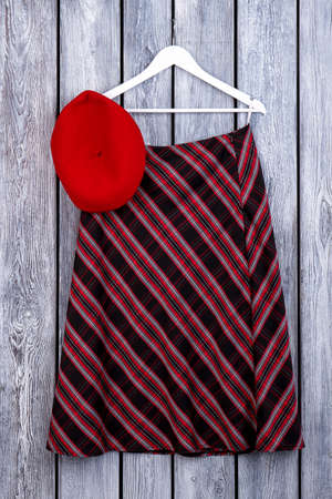 Women striped skirt hanging on hanger. Female red beret and skirt, wooden background. Female classy outfit.
