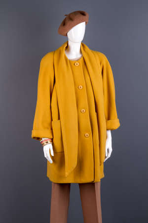 Women fashionable yellow topcoat on mannequin. Female mannequin wearing stylish autumn outerwear, grey background.