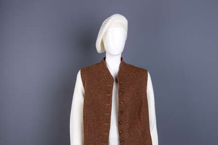 Female white beret and brown waistcoat. Dummy wearing women autumn apparel, grey background.