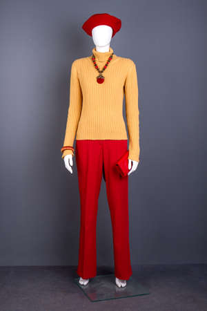 Full length mannequin in fashion women attire. Female mannequin dressed in yellow turtleneck sweater and red trousers. Red beret and accessories for stylish women. Stock Photo