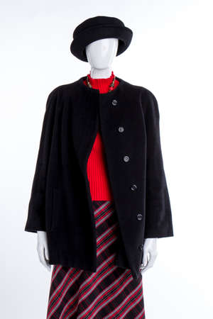 Black hat, overcoat and red sweater. Female mannequin dressed in black top coat and striped skirt, white background. Beautiful attire for ladies. Stock Photo