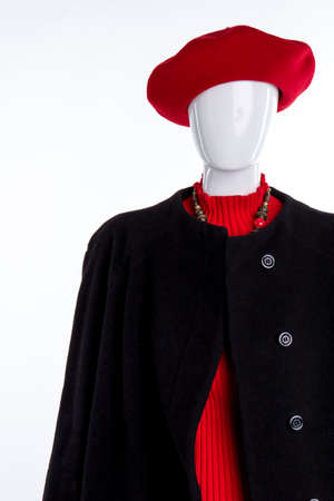 Red beret, sweater and black coat. Close up female mannequin dressed in red hat and black overcoat, white background. Ladies elegance and style.