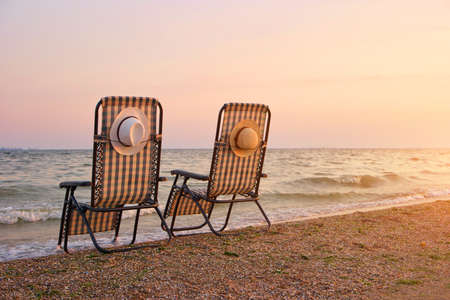 Recliner beach seatings while sunset. Checkered deckchair on beach in evening.