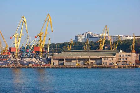 Sea port in a city. Industrial equipment of the sea port - wharf cranes. Banco de Imagens