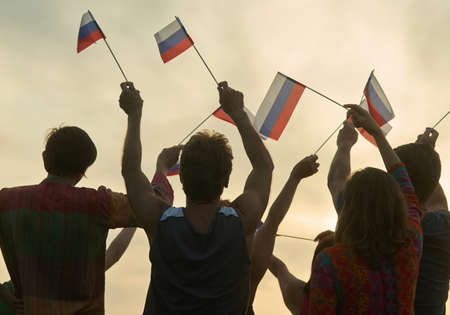 Crowd with russian flags. Evening sunny sky background.