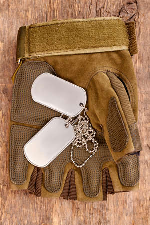 Dog tags on military fingerless glove. Close up, top view. Wooden desk surface background.