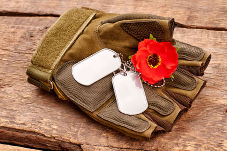 Dog tags and red poppy on military fingerless glove. Wooden desk surface background.