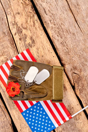 US military army soldier items and flag. Close up, top view. Wooden desk surface background with copyspace. Stock Photo
