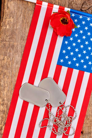 Dog tags, red poppy and american usa flag. Wooden desk bakground.