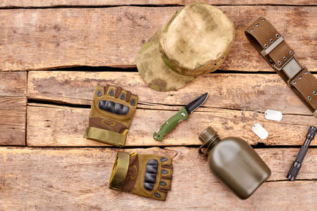 Military accessories items on wood. Top view, flat lay. Soldiers cap, gloves and bottle.