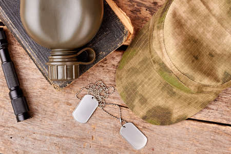 Personal items of a soldier, flat lay. Top view. Wooden background.