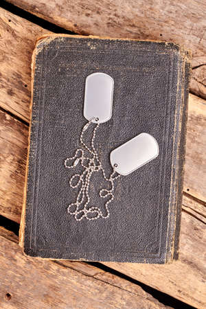 Old book and dog tags. Top view, flat lay. Wooden desk background. Stock Photo