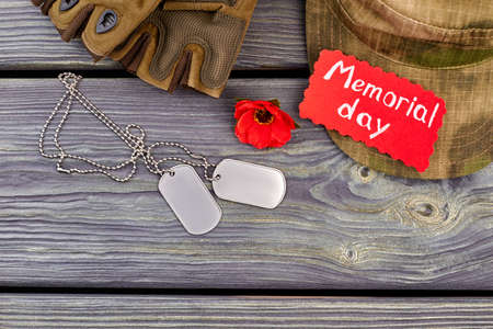 Military army accessories for memorial day. Dog tags, red poppy, cap and gloves. Grey wooden desk background.