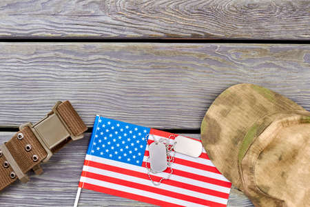 American flag, nylon strap, dog tags and military cap. Top view, flat lay, Wooden desk background.